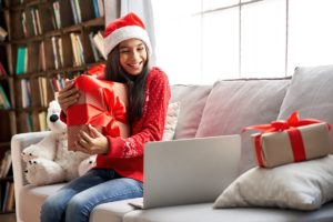 young girl with santa hat on sits on a couch holding a christmas present to a laptop screen