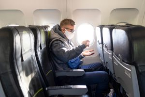 young man on plane applies hand sanitizer