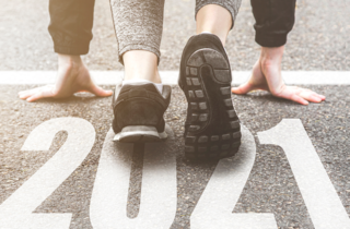 feet of a runner standing over 2021 on the pavement