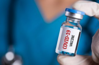 """care team wonrker holding a vial with """"COVID-19 vaccine"""" printed on it"""
