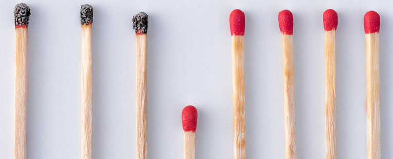 Line of burned matchsticks with several unburned matches to signify the COVID-19 death rate.