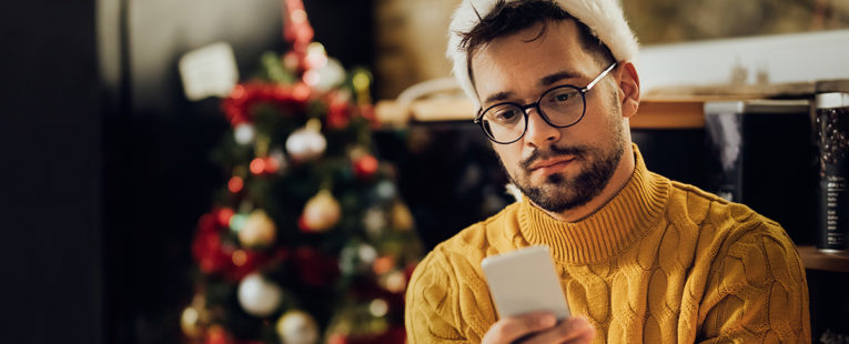 man with santa hat on looks disappointedly at his phone in front of a Christmas tree