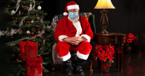 Santa sitting in chair with mask on