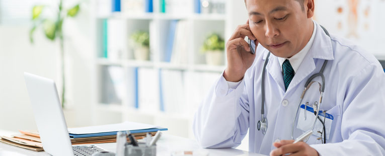 Male Asian doctor at desk speaking on phone with notepad and laptop in front of him
