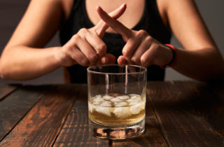"woman behind an glass of alcohol with ice, fingers crossed as if to say ""no"""