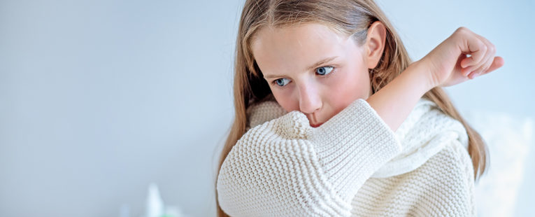 Girl in white sweater coughs into elbow