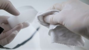 two latex gloves hands clean a face shield with wipes