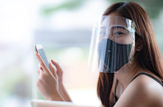 girl wearing a mask and a faceshield reads her cellphone