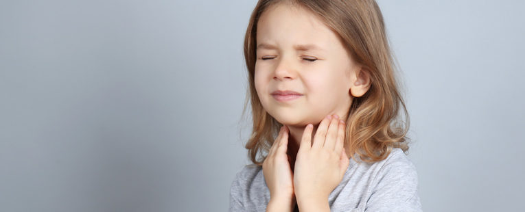 little girls holds her throat in obvious pain