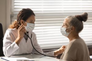 masked female doctor uses a stethescope on a senior woman in an exam room