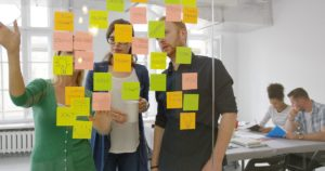 two women and a man stand in from of a glass wall full of post-it's collaborating on ideas