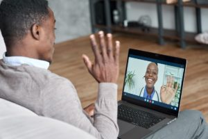 man waves at this laptop where a female doctor waves back through a virtual office visit