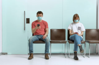 man and a woman sit wearing masks in a waiting room