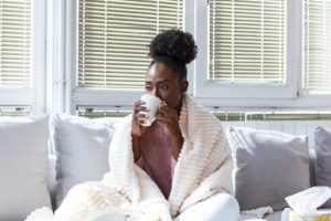 woman on a couch drinks from a mug wrapped in a blanket