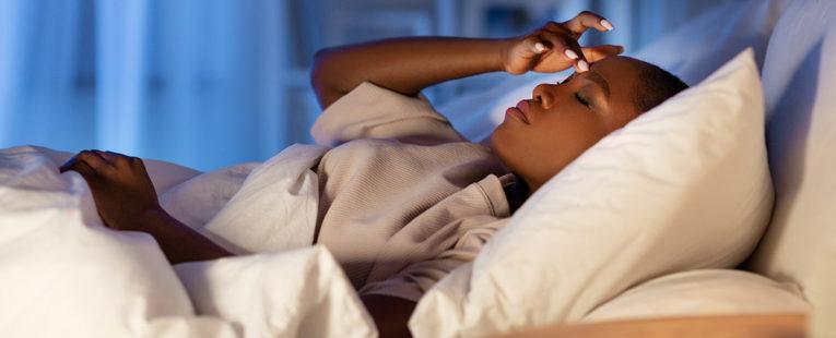 woman lies awake in bed
