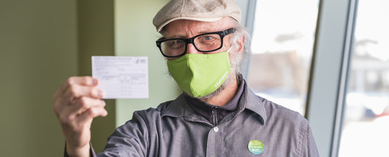 Kirk Wessler wearing mask holding COVID-19 vaccination card.