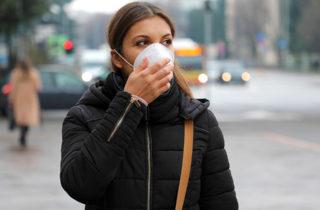 A masked woman walks outside on a city street.