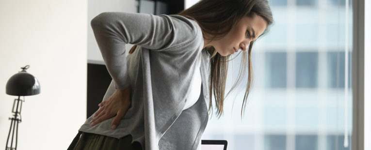 Woman standing at desk holding lower back as if in pain