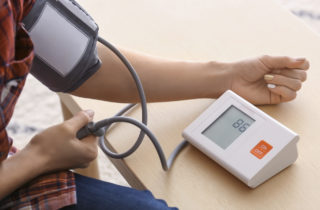 Young woman measuring his blood pressure at home