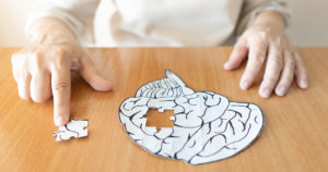 Elderly woman hands putting missing white jigsaw puzzle piece down into the place as a human brain shape. Creative idea for memory loss, dementia, Alzheimer's disease and mental health concept.