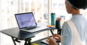 woman stands working on a laptop with the use of a standing desk