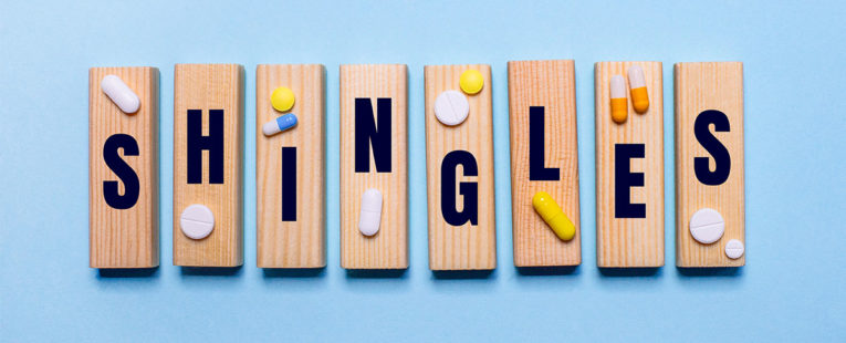"""The word """"shingles"""" is spelled out on wooden tiles with medicine placed on top."""