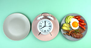empty dinner plate and plate with food. Clock in the middle
