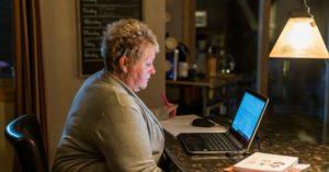 woman sitting at desk looking at computer
