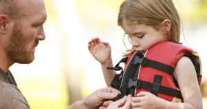 father helping daughter with life jacket