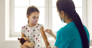 Vaccination concept. Little kid in medical face mask getting Covid-19 or flu vaccine at clinic. Woman who works as nurse or doctor at hospital disinfects skin on child's arm before giving injection