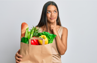 woman with shopping bag full of healthy food looks to be thinking