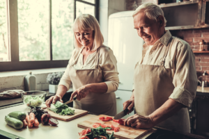 senior couple in aprons smiling while cooking together