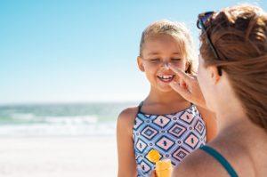 mom putting sunscreen on kid