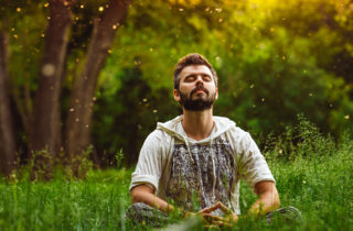 Man practicing progressive muscle relaxation sitting in a field with eyes closed