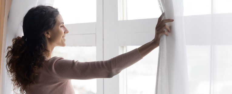 Woman cancer survivor looking hopeful out her living room window