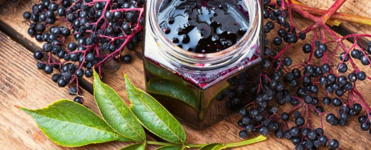 elderberries displayed on a cutting board with a jar of elderberry jam in the center of the image and a sprig of leaves in the lower left corner
