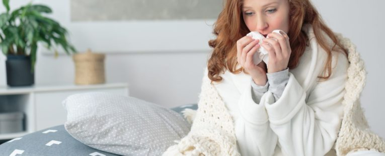 Sick woman sitting on bed with blanket over shoulders as she blows her nose into a facial tissue