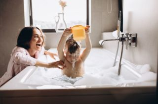 Child taking a bath with his mom