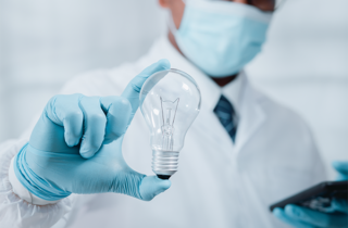 Doctor in surgical mask holds light bulb in foreground with blue gloved hand