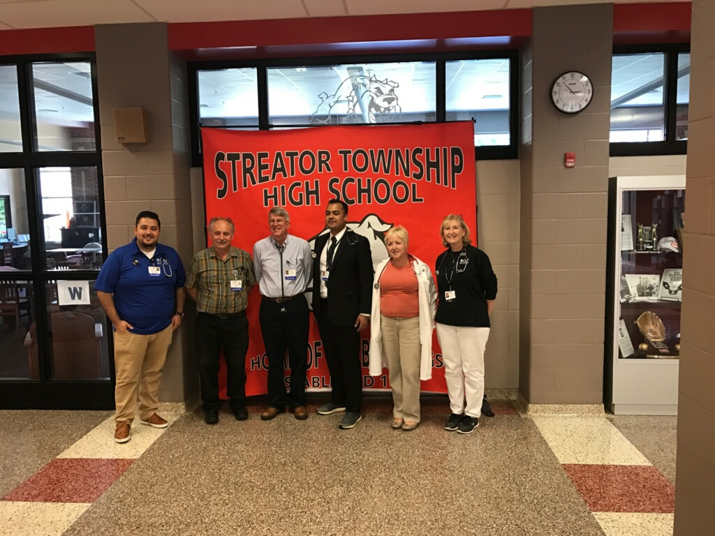 OSF doctors in front of Streator Township High School banner