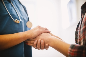Nurse Navigator Holding Hands with Patient