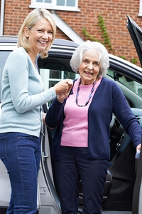 Adult daughter helping elderly mother out of a van.