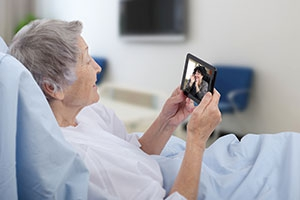 Senior female patient in hospital video chats with daughter on tablet.