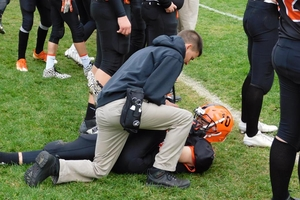 Athletic Trainer assisting a football player on a field.