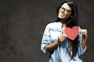 woman posing with a cut-out heart.