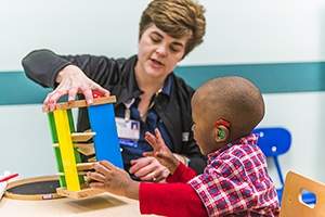 Pediatric rehabilitation specialist working with young boy