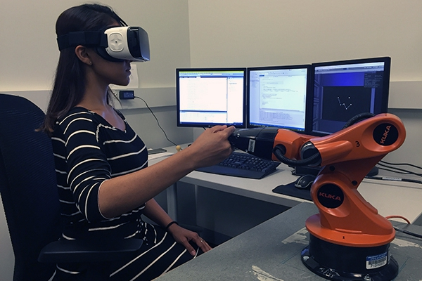 Young woman using virtual reality simulation equipment in a lab setting.