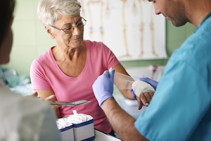 Senior woman receiving wound care.