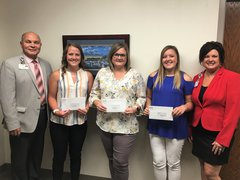 Ken Beutke (L), president of OSF Saint Elizabeth, and Cherie Reynolds (R), director of development with OSF Foundation, present the recipients (L:R) McKenna Campbell, Sandy Northcutt, and Maleah Greene with the 2019 educational loan assistance awards.