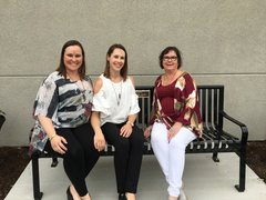 "Photo of Kayla Moore & Kristin Burnside, Daughters Gene, and Holly Grobe wife of Gene, sitting on the Eugene ""Gene"" Grobe Memorial Bench."